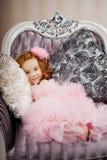 Criança em uma cadeira em um vestido agradável Fotos de Stock Royalty Free