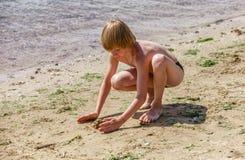 Criança em uma praia que é areia jogada Imagem de Stock