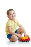 Criança engraçada que joga com o brinquedo do caminhão isolado no branco Fotografia de Stock