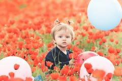 Criança engraçada que mantém um balão exterior no campo da papoila Imagens de Stock Royalty Free