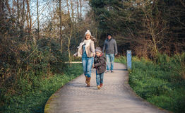 Criança feliz e mulher que correm na floresta Fotos de Stock Royalty Free