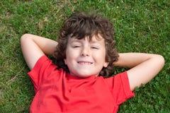 A criança feliz encontrou-se para baixo na grama Foto de Stock