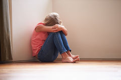 Criança infeliz que senta-se no assoalho no canto em casa Imagens de Stock