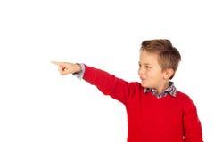 Criança loura com jérsei vermelho que aponta com seu dedo Fotografia de Stock