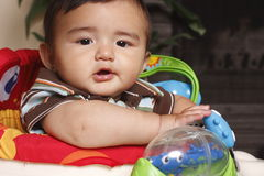 Criança na cadeira com brinquedos Imagem de Stock Royalty Free