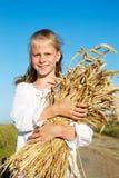 Criança na camisa branca que guarda as orelhas do trigo nas mãos Fotografia de Stock