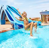 Criança na corrediça de água no aquapark. Imagem de Stock