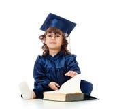 Criança na roupa do academician com livro Fotografia de Stock Royalty Free
