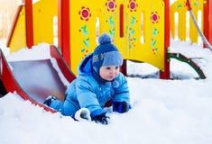 Criança no campo de jogos no inverno Fotografia de Stock