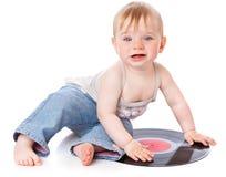 A criança pequena com um registro de gramofone preto Imagens de Stock Royalty Free