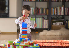 Criança pequena de riso bonita, menina moreno da idade pré-escolar que joga com os blocos coloridos que sentam-se em um assoalho Foto de Stock Royalty Free
