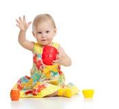 Criança pequena engraçada que joga com brinquedo do copo Foto de Stock Royalty Free