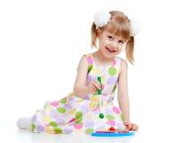 Criança pequena engraçada que joga com brinquedos coloridos Fotos de Stock Royalty Free