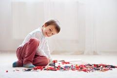 A criança pequena que joga com lotes do plástico colorido obstrui interno Fotografia de Stock Royalty Free