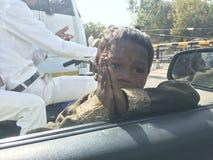 A criança pobre indiana reza ao carro dentro dos povos diz dá-me por favor o dinheiro Imagens de Stock