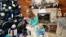 A criança prejudicial, uma menina levanta as caras, o comportamento mau da criança no party girl que senta-se entre brinquedos no video estoque