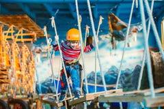 Criança que aprecia um dia e um jogo de verão A criança feliz que tem o divertimento no parque da aventura, escalando ropes Fotos de Stock Royalty Free