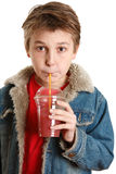 Criança que bebe o suco de fruta fresca através de uma palha Imagem de Stock Royalty Free