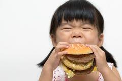 Criança que come o hamburguer grande Fotos de Stock
