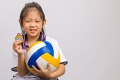 Criança que guarda a medalha da bola e de ouro, isolada no branco Fotos de Stock Royalty Free