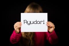 Criança que guarda o sinal com palavra espanhola Ayudar - ajuda Imagens de Stock Royalty Free