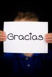 Criança que guarda o sinal com palavra espanhola Gracias - obrigado Fotografia de Stock