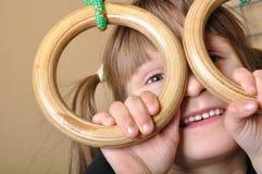 Criança que joga em anéis ginásticos Fotografia de Stock Royalty Free