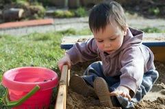 Criança que joga na caixa de areia Fotografia de Stock