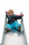 Criança que joga na corrediça Fotos de Stock Royalty Free