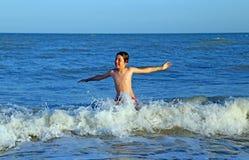 Criança que joga no mar que salta as ondas do mar agitado Imagem de Stock Royalty Free