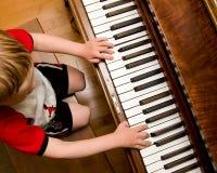 Criança que joga o piano Imagem de Stock