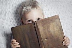 Criança que lê o livro velho Fotos de Stock Royalty Free
