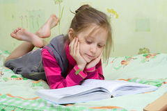 Criança que lê um livro Imagens de Stock Royalty Free