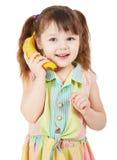 A criança usa uma banana como um telefone móvel Fotografia de Stock