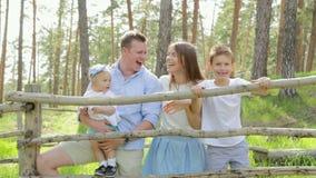 Crianças caucasianos novas felizes que comunicam-se e que laughting com pais no parque video estoque