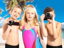 Crianças com foto e câmara de vídeo na praia. Fotografia de Stock Royalty Free