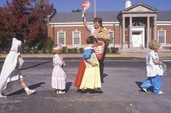 Crianças de ajuda do protetor de cruzamento da escola Imagens de Stock Royalty Free