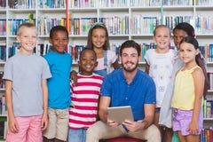 Crianças de ensino do professor na tabuleta digital na biblioteca Fotos de Stock