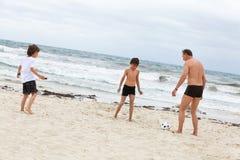 Crianças do pai dois da família que jogam o futebol na praia Foto de Stock
