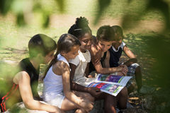 Crianças e livro de leitura da educação, das crianças e das meninas no parque Imagens de Stock Royalty Free