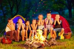 Crianças engraçadas com as caras pintadas nas mãos que sentam-se em torno do fogo do acampamento Fotos de Stock Royalty Free