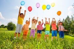 Crianças felizes com balões e braços acima no céu Fotos de Stock Royalty Free