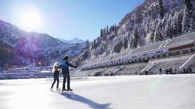Crianças felizes menina e patinagem no gelo do menino na pista exterior video estoque