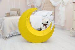 Crianças interiores Sala da luz branca com um berço, o brinquedo da lua, um urso de peluche Foto de Stock