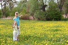 Crianças no campo com flor. Imagem de Stock Royalty Free