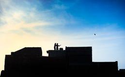 Crianças no jogo do telhado com papagaios Fotos de Stock