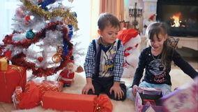 Crianças que abrem seus presentes do Natal video estoque