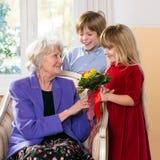 Crianças que dão flores da avó Fotografia de Stock Royalty Free