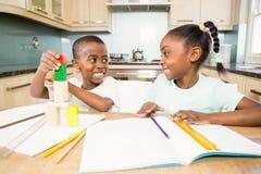 Crianças que fazem trabalhos de casa na cozinha Imagem de Stock