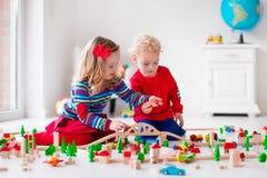 Crianças que jogam com estrada de ferro e trem do brinquedo Fotografia de Stock